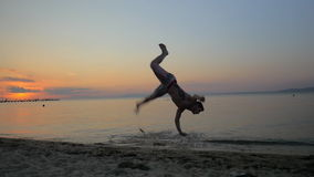 Mann, der Akrobatik an der Küste während des Sonnenuntergangs zeigt