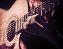 Mann, der Akustikgitarre auf dunklem Hintergrund spielt Ein musikalisches concep Stockbild