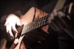 Mann, der Akustikgitarre auf dunklem Hintergrund spielt Ein musikalisches concep Lizenzfreies Stockfoto