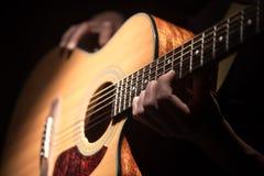 Mann, der Akustikgitarre auf dunklem Hintergrund spielt Ein musikalisches concep Stockfotografie