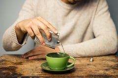 Mann, der Alkohol seinem Kaffee hinzufügt Stockfoto