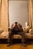 Mann, der alleine auf dem Sofa sitzt lizenzfreie stockfotos