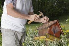 Mann, der alte Vogel Hausnahaufnahme repariert Lizenzfreies Stockbild