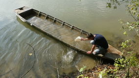 Mann, der altes versunkenes Fischerboot leert stock footage