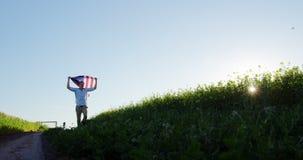 Mann, der amerikanische Flagge und Betrieb auf dem Gebiet hält stock video