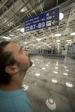 Mann, der Anschlagtafel im Flughafen schaut Stockfotografie