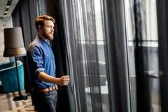 Mann, der Ansicht vom luxuriösen Hotelzimmer genießt lizenzfreie stockbilder