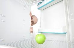 Mann, der Apfel im Kühlraum betrachtet Stockfoto