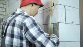Mann in der Arbeitsabnutzung und in Reparierenschiene der roten Kappe metallmit Klammern auf Blockwand stock video