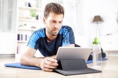 Mann, der auf Übung Mat While Using sein Tablet liegt Stockbilder