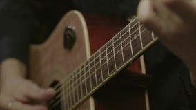 Mann, der auf Akustikgitarre spielt stock footage