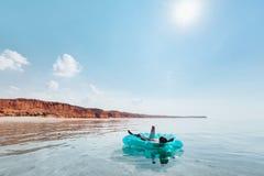 Mann, der auf aufblasbarem Ring auf dem Strand sich entspannt lizenzfreies stockbild