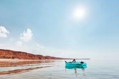 Mann, der auf aufblasbarem Ring auf dem Strand sich entspannt lizenzfreie stockfotografie