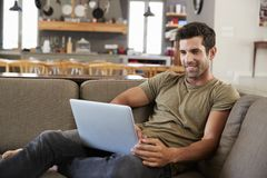Mann, der auf Aufenthaltsraum Sofa Using Laptop sitzt lizenzfreie stockfotos