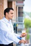Mann, der auf Balkon trinkt stockbilder