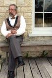 Mann, der auf Bank sitzt Stockbild