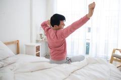 Mann, der auf Bett nachdem dem Aufwachen ausdehnt lizenzfreie stockfotografie