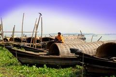 Mann, der auf Bootsdecken sitzt Lizenzfreies Stockfoto
