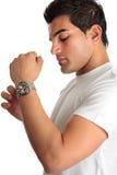 Mann, der auf Chronographuhr sich setzt Stockbild