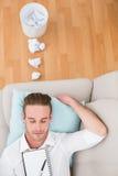 Mann, der auf Couch mit Verfasserblock stillsteht stockfotos