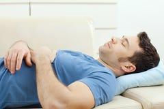 Mann, der auf Couch schläft Lizenzfreie Stockfotografie