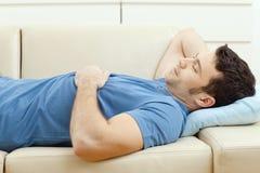 Mann, der auf Couch schläft Stockfotografie