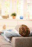 Mann, der auf Couch sich entspannt Stockfoto