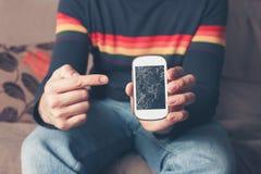Mann, der auf defektes intelligentes Telefon zeigt Stockfotografie