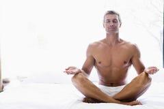 Mann, der auf dem Bett tut Yoga sitzt Lizenzfreie Stockfotos