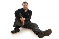 Mann, der auf dem Boden sitzt Stockbild