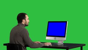 Mann, der auf dem Computer auf einem grünen Schirm, Farbenreinheitsschlüssel schreibt Blue Screen-Modell-Anzeige stock footage