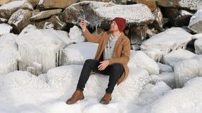 Mann, der auf dem Eis sitzt und am Telefon spricht lizenzfreies stockbild