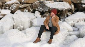 Mann, der auf dem Eis sitzt und am Telefon spricht stockbild