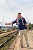 Mann, der auf dem Eisenbahn-Bahnstationlächeln per Anhalter fährt Lizenzfreies Stockbild