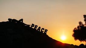 Mann, der auf dem Felsen genießt Sonnenuntergang liegt Lizenzfreie Stockbilder