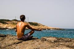 Mann, der auf dem Felsen-Ufer meditiert Stockfoto