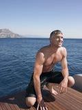 Mann, der auf dem Fußbodenbrett der Yacht sich duckt Stockfoto