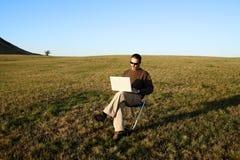 Mann, der auf dem Gebiet mit Laptop sitzt Stockbild