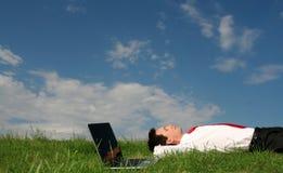 Mann, der auf dem Gras liegt Stockbild