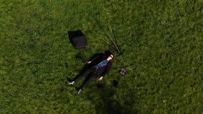 Mann, der auf dem Gras umgeben durch einen Stativ, Blitze und Rucksäcke liegt stock video footage