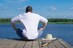 Mann, der auf dem Pier, verärgertes, schlechtes Fischen, Freien, Wasserhintergrund sitzt lizenzfreies stockfoto