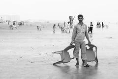 Mann, der auf dem Strand hält Stühle steht Stockfotografie