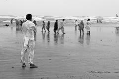 Mann, der auf dem Strand hält Stühle steht Lizenzfreie Stockfotografie