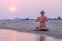 Mann, der auf dem Strand meditiert Lizenzfreies Stockfoto