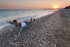 Mann, der auf dem Strand sich entspannt Stockbild