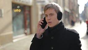Mann, der auf dem Telefon und dem Lächeln spricht stock footage