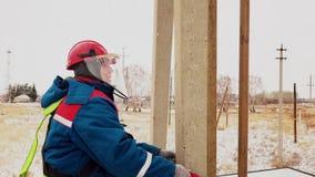 Mann, der auf den Pfosten für Reparaturspannungskabel an der elektrischen Station umzieht stock footage