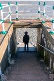 Mann, der auf den Schritten blicken in Richtung des Meeres steht Stockfoto