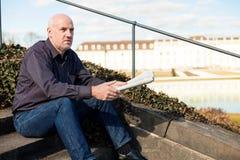 Mann, der auf den Schritten lesen eine Zeitung sitzt Stockfotos