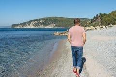 Mann, der auf den Strand geht Schönes Pebble Beach, blauer Himmel und Meer lizenzfreies stockfoto